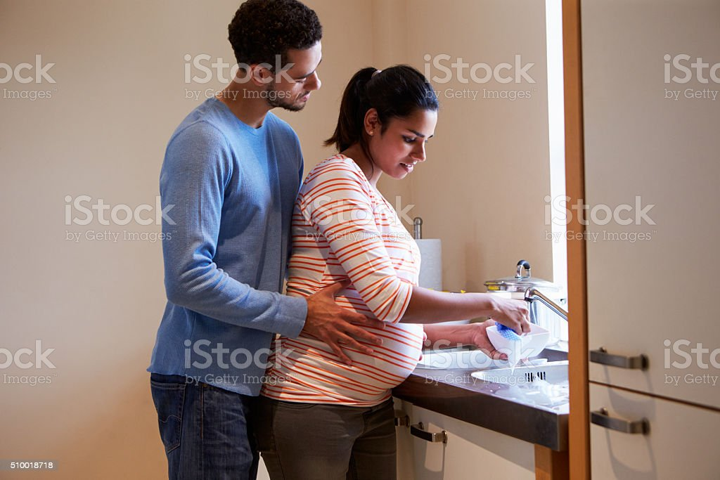 Pregnant Woman With Partner Washing Dishes In Kitchen Sink stock photo