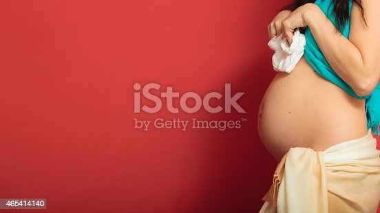 istock pregnant woman with small shoes for unborn baby 465414140