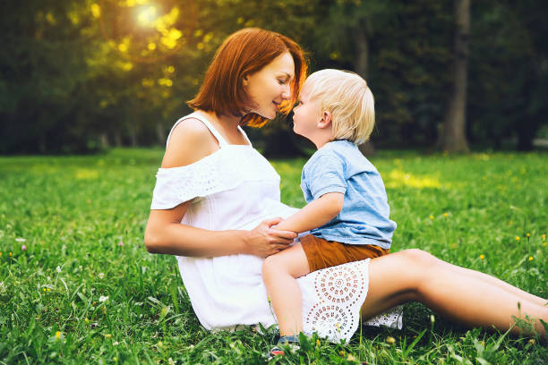 zwangere vrouw met peuter kind buitenshuis. - mini amusementpark stockfoto's en -beelden