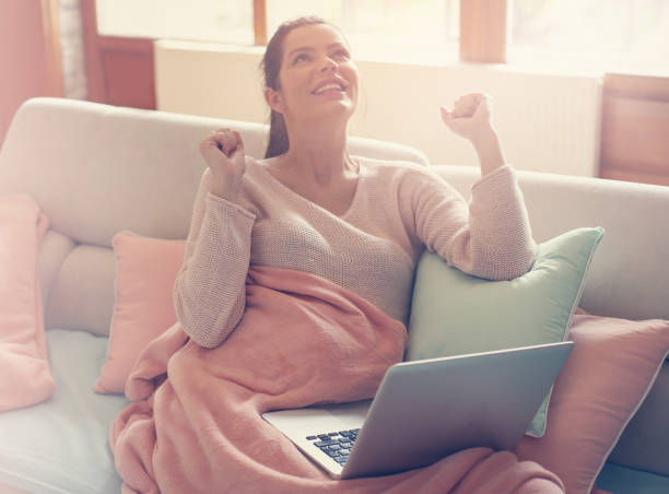 schwangere frau arbeitet auf einer couch. - schwanger werden rechner stock-fotos und bilder