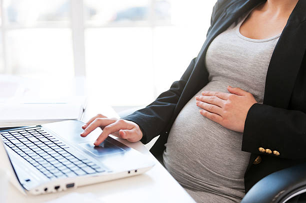 Pregnant woman working on laptop. stock photo