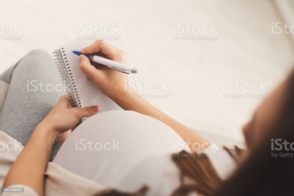 Pregnant woman writing names for her baby stock photo