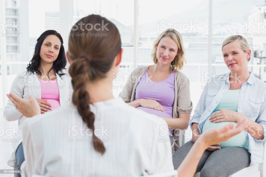 Pregnant women listening to gesturing doctor at antenatal class stock photo