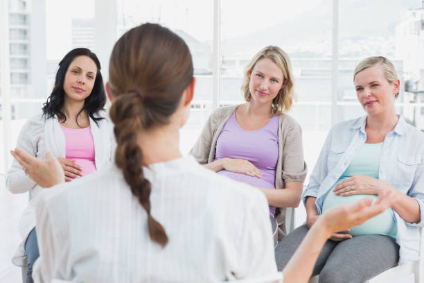 pregnant women listening to gesturing doctor at antenatal class - midwife stock pictures, royalty-free photos & images