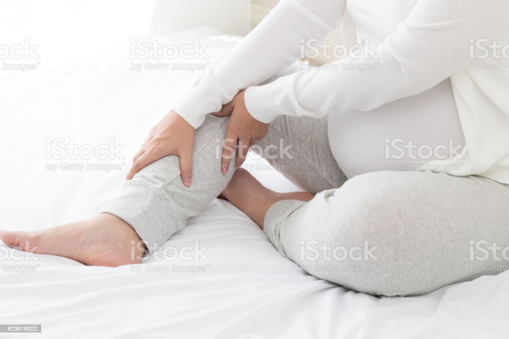 Pregnant women with cramp in leg stock photo