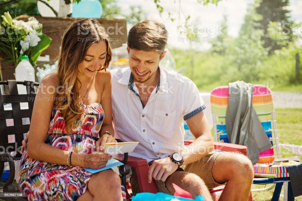 Pregnant young couple reading greeting card at baby shower outdoors. stock photo