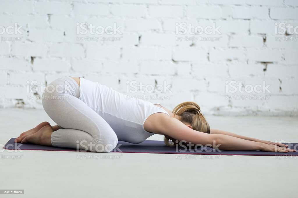 Pregnant young woman doing prenatal Child Yoga Pose, Balasana stock photo