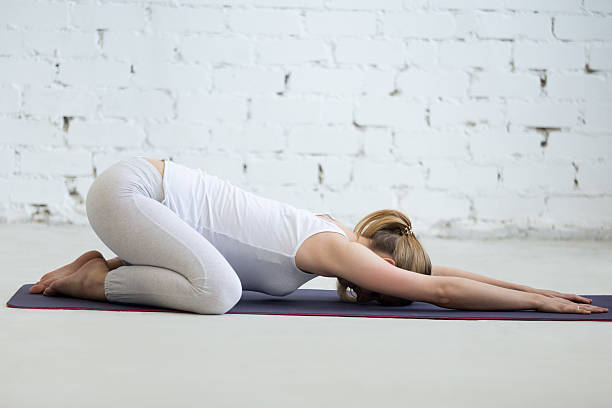 Pregnant young woman doing prenatal Child Yoga Pose, Balasana Pregnancy Yoga and Fitness. Portrait of young pregnant yoga model working out in loft with white walls. Pregnant fitness person practicing yoga at home. Prenatal Balasana, Child Pose childs pose stock pictures, royalty-free photos & images