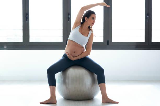 Schwangere junge Frau macht Entspannungsübungen mit einem Fitness-Pilates-Ball zu Hause. – Foto