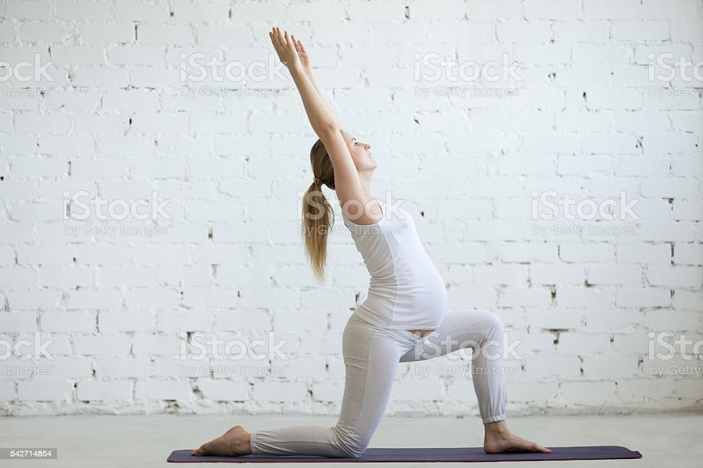 Pregnant young woman doing yoga Virabhadrasana 1 pose stock photo