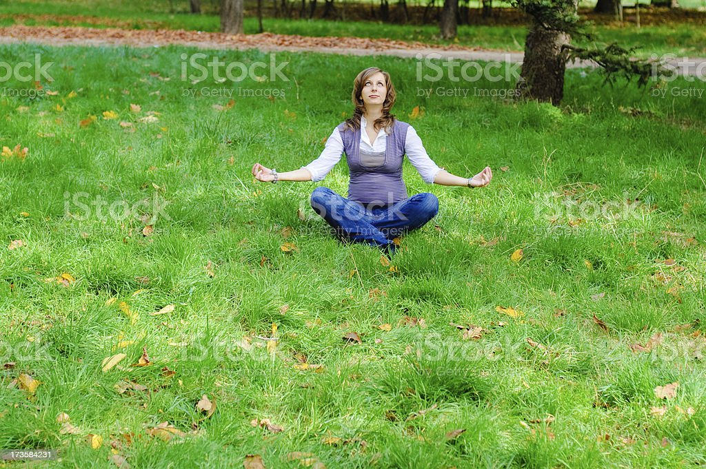 pregnant young woman relax on green grass with yellow leaves royalty-free stock photo