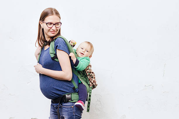 pregnant young woman with her little son in baby carrier - rückentrage stock-fotos und bilder