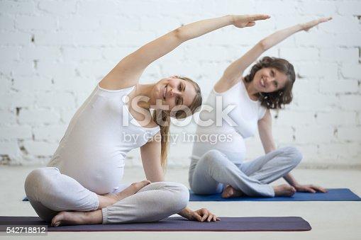 istock Pregnant young women doing prenatal yoga. Bending in easy pose 542718812