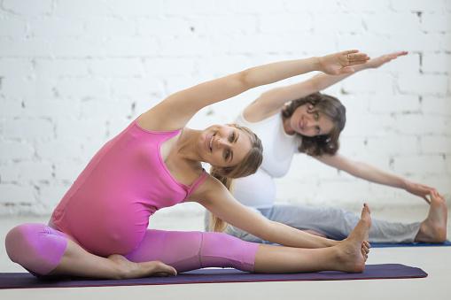Pregnant Young Women Doing Prenatal Yoga Headtoknee ...