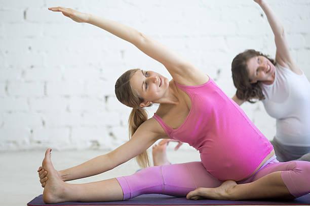 Pregnant young women doing prenatal yoga stock photo