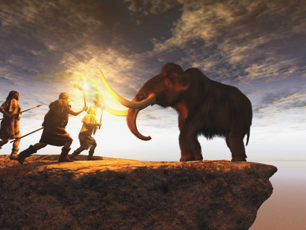 prehistoric men hunting a young mammoth - ancient stock photos and pictures