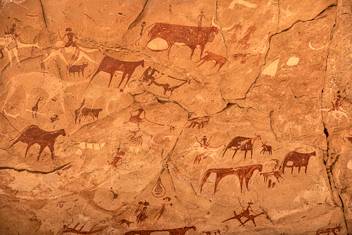 Prehistoric rock painting art in a cave in the remote Ennedi Mountains in the Sahara desert, North-East Chad. This famous rock art images can be dated to around 5000 BC onwards. The Ennedi massif was declared as an UNESCO World Heritage site in 2016.