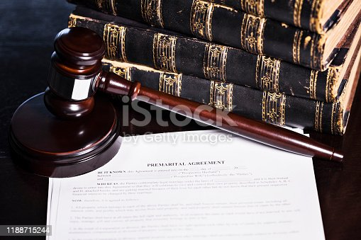 Close up of a generic premarital agreement with law books and a gavel.