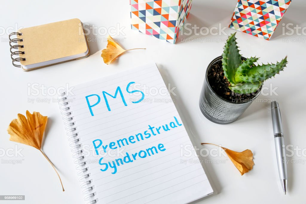 PMS Premenstrual Syndrome written in notebook stock photo