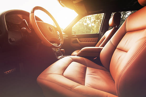 premium car interior, brown leather at sunset - brutzeln stock-fotos und bilder