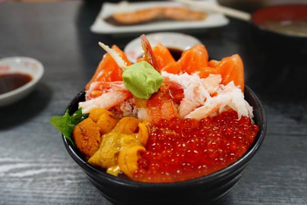 premium set rijstkom met verse rauwe zeevruchtenmix, krab, zalm, zalmeieieren, uni serveer samen met wasabi, japans lekker of kaisen don - krab gerecht stockfoto's en -beelden