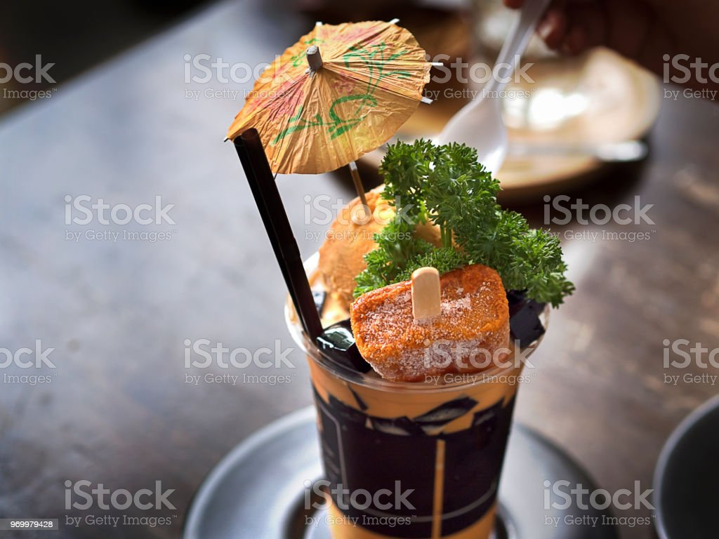 Premium Thai tea with milk or Thai tea latte frappe served with Ice cream and mint on wooden table in a cafe or coffee shop for dessert or drinks stock photo