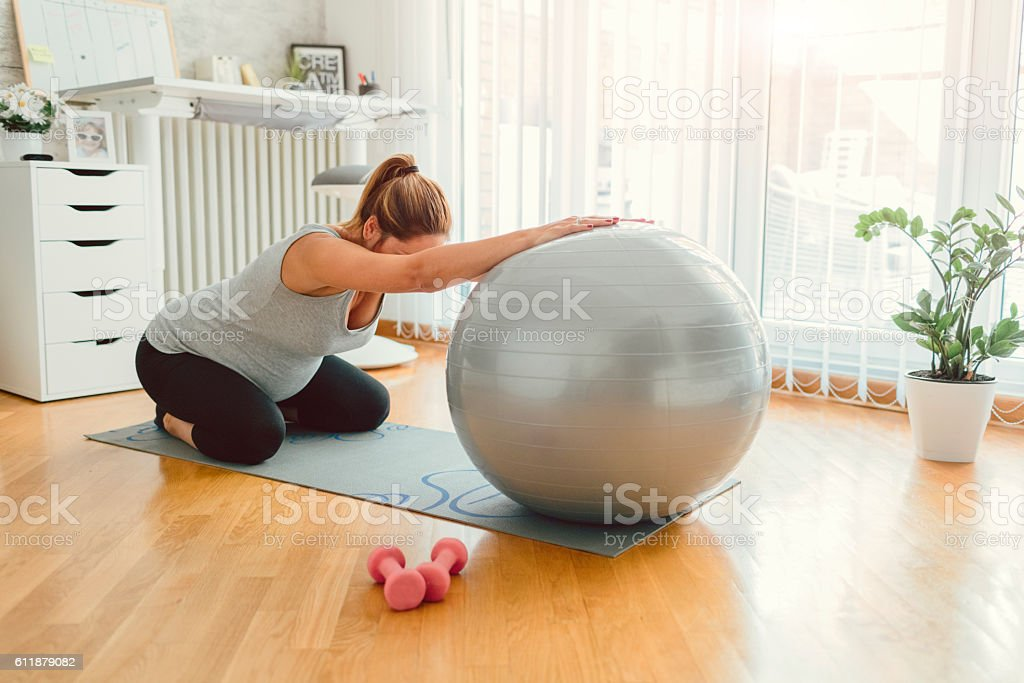 30 weeks pregnant woman exercising at home. Sitting on exercise mat...