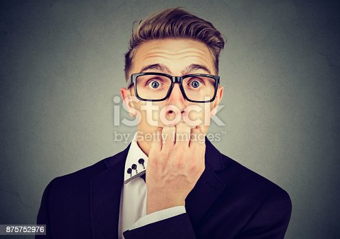 istock Preoccupied anxious business man in glasses biting his fingernails looking at camera 875752976