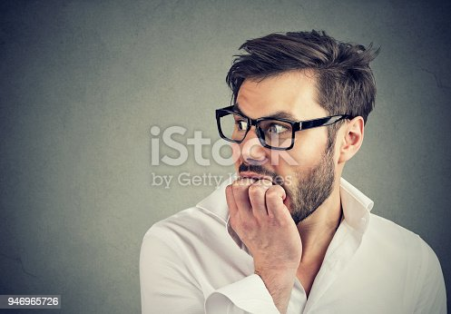 istock Preoccupied anxious man biting his fingernails looking to the side 946965726