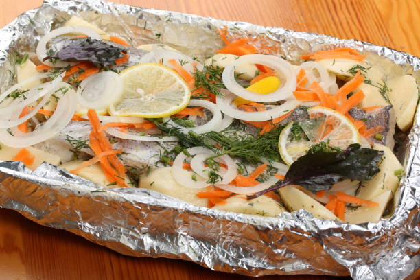 vorbereitung einer marinierter seehecht mit kartoffeln im ofen backen - alufolie backofen stock-fotos und bilder