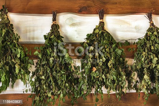 istock Preparation and drying of birch brooms for a sauna. New brooms hang on the wall of the boards in the bath 1159403831