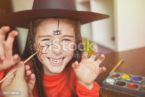 istock preparation for Halloween. child in a witch outfit doing face painting. cute spider. idea of simple suit, diy 1022199032
