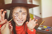 preparation for Halloween. child in a witch outfit doing face painting. cute spider. idea of simple suit, diy
