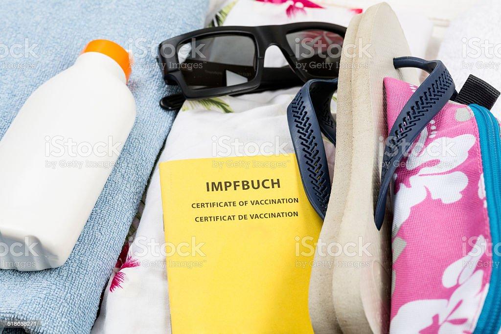 Preparation for holiday, luggage with swimwear, towel, sunglasses, suncream stock photo