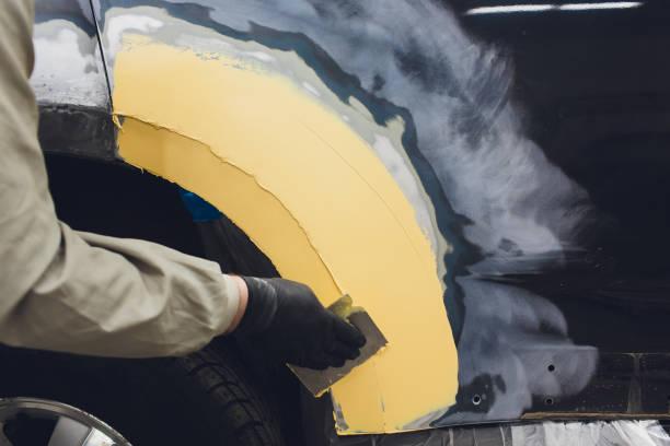 Vorbereitung auf die Lackierung eines Fahrzeugelementes mit dem Absender durch einen Servicetechniker, der ausnivelliert wird, bevor er bei einem Unfall in der Werkstatt einen Grausamenten nach Beschädigung eines Teils der Karosserie anlegt. – Foto