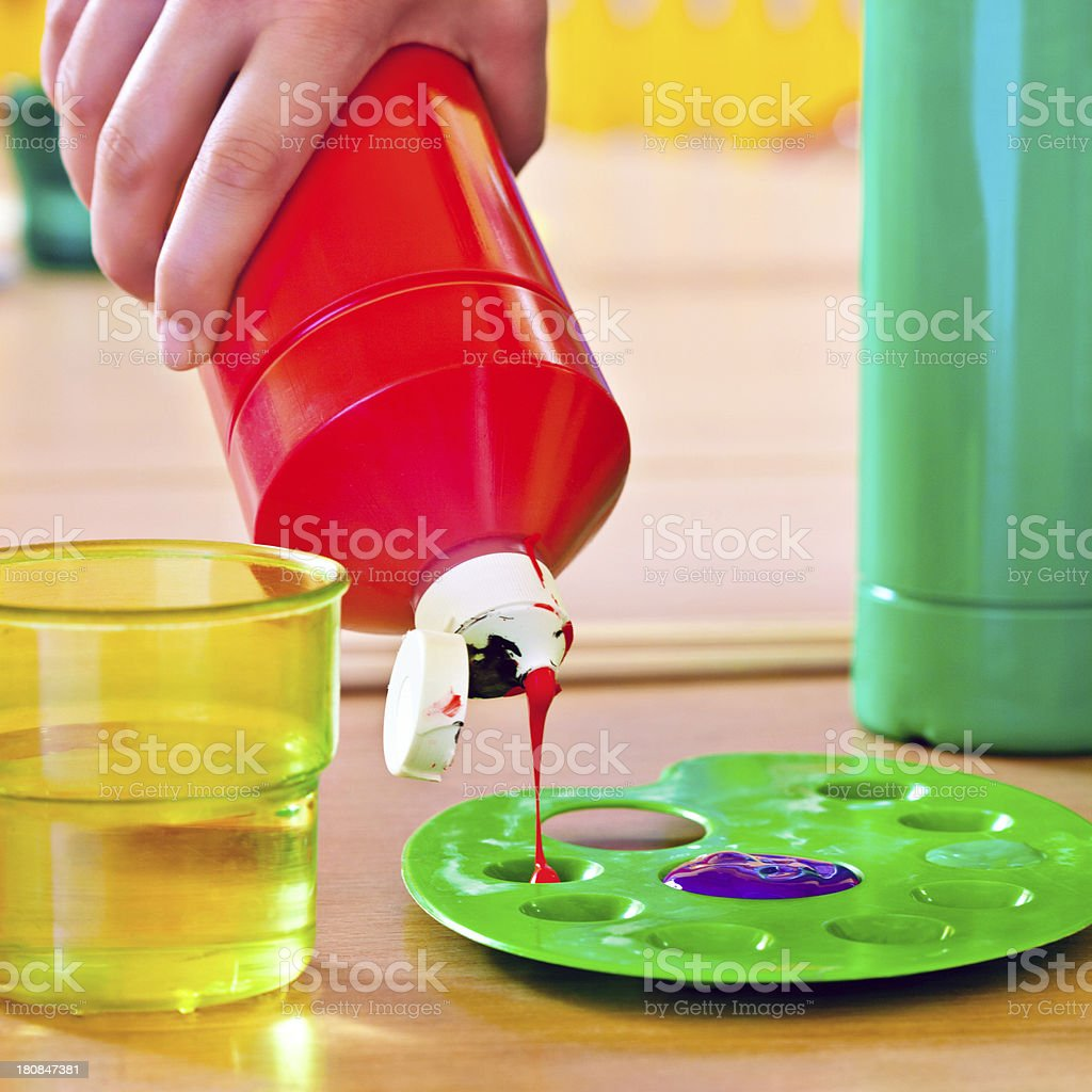 Preparation for painting Human hand pouring paint from bottle on the palette.  Acrylic Painting Stock Photo