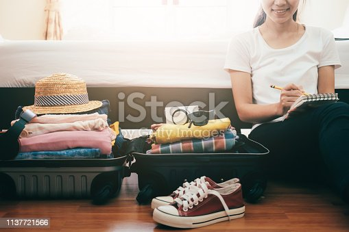 Preparation for vacation or travel. Packing his clothes and stuff into large opened suitcase that almost already full.