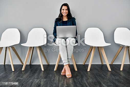 Studio shot of a young businesswoman using a laptop while waiting in line against a grey background
