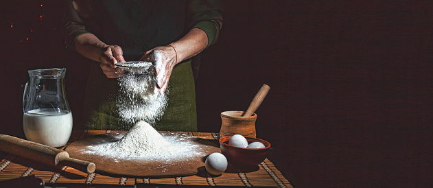 istock Preparation of bread dough. Bakery, baker's hands, flour is poured, flying flour 909870324