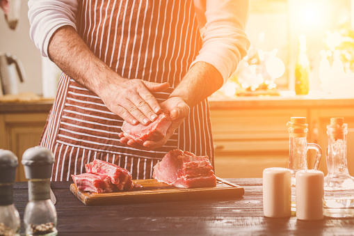 Preparation of dinner. Cooking, processing of meat beef, tenderloin . Person man's hands marinates meat - sprinkles with salt, pepper