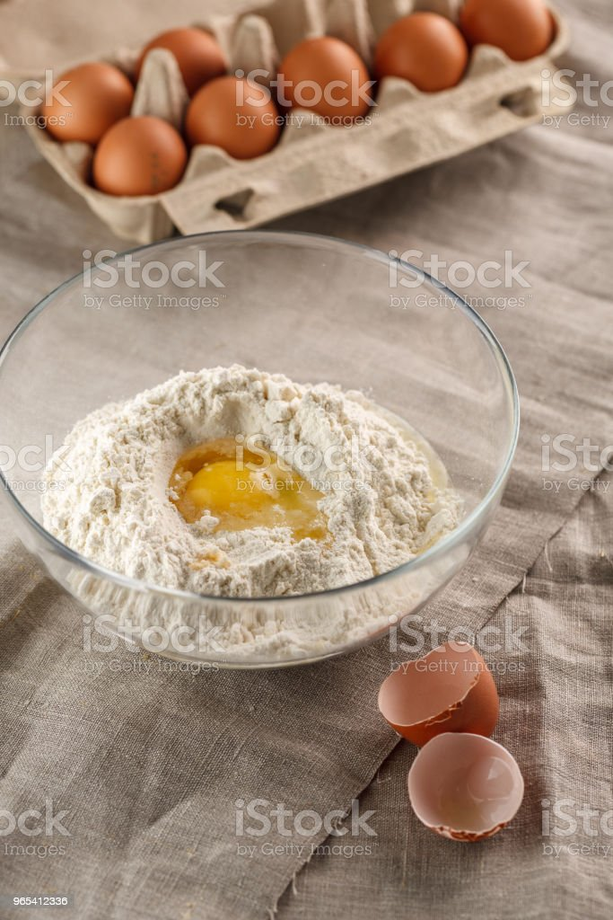 preparation of dough for flat bread. broken egg and flour in a glass bowl royalty-free stock photo