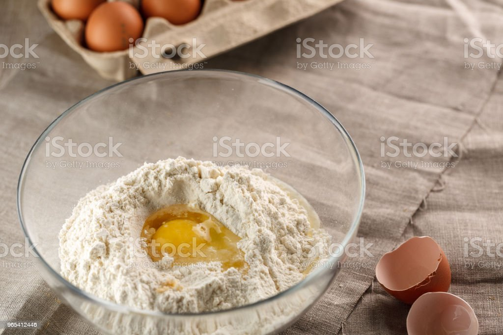 preparation of dough for flat bread. broken egg and flour in a glass bowl zbiór zdjęć royalty-free