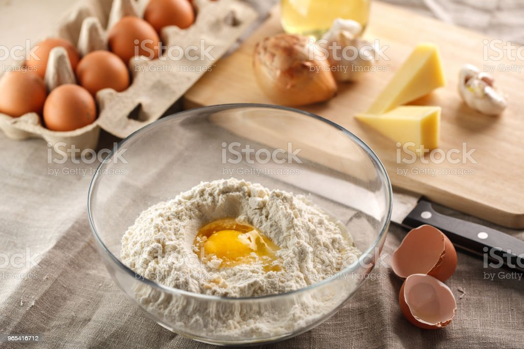 preparation of dough for flat bread. broken egg and flour in a glass bowl. flat bread with onion, cheese and garlic zbiór zdjęć royalty-free