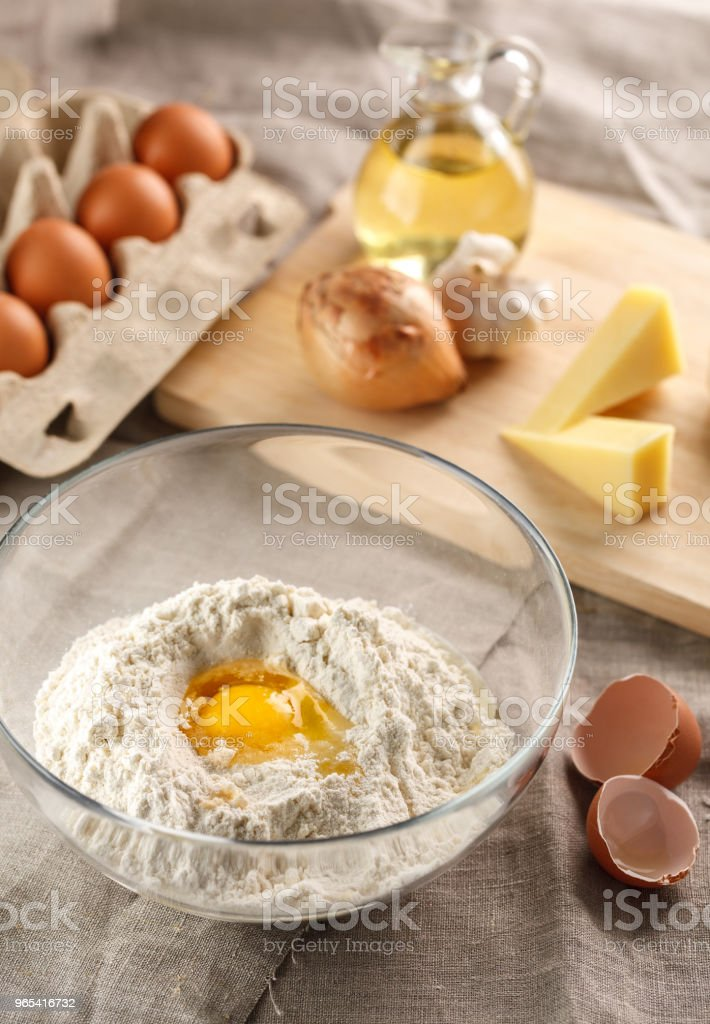 preparation of dough for flat bread. broken egg and flour in a glass bowl. flat bread with onion, cheese and garlic royalty-free stock photo