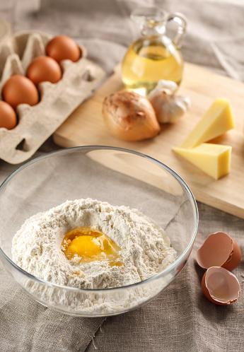 플랫 빵 반죽의 준비입니다 깨진된 계란 고 유리 그릇에 밀가루입니다 양파 치즈와 마늘 플랫 빵 가루로 빻은에 대한 스톡 사진 및 기타 이미지