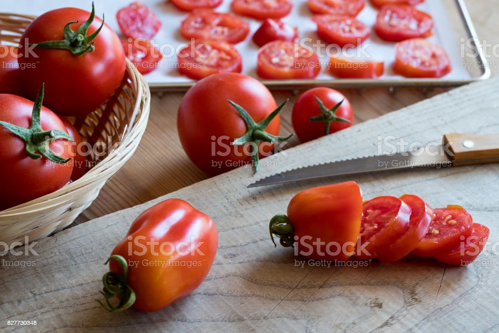Preparation of dried tomatoes - slicing San Marzano tomatoes stock photo