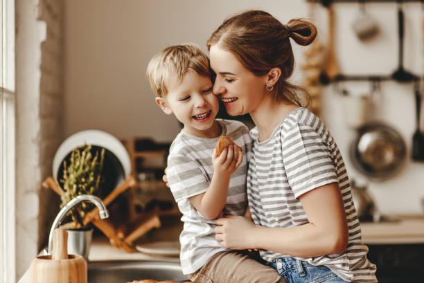preparação do café da manhã em família. mãe e filho cortado pão e comer biscoitos com leite pela manhã - mãe - fotografias e filmes do acervo