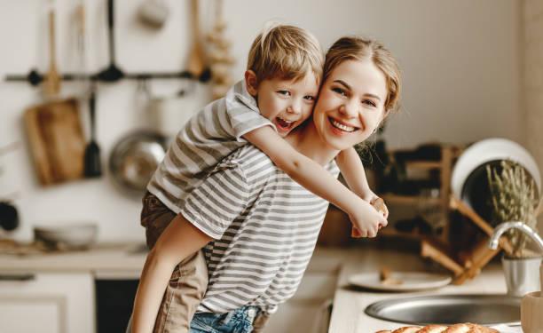 Zubereitung des Familienfrühstücks. Mutter und Sohn schneiden Brot und essen Kekse mit Milch am Morgen – Foto