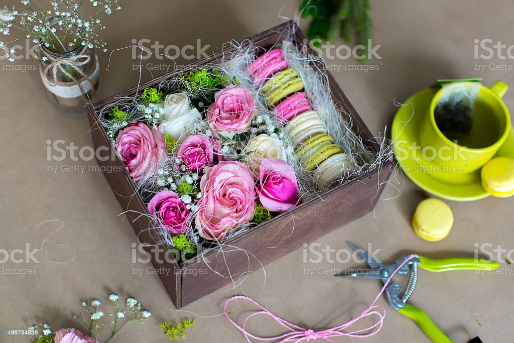 Preparation of flower box with macaroons, top view of florist...
