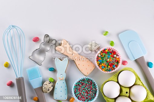 istock Preparation of gingerbread cookies. Easter cookies in the shape of  a  funny  rabbit , tools necessary to make gingerbread pastry, colored sprinkles. Easter concept. 1093926154